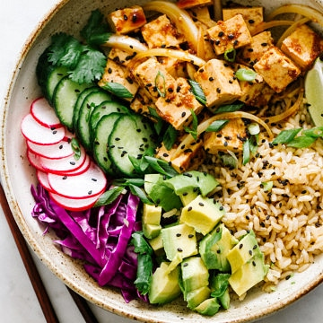 top down view of vegan poke bowl with tofu in a rustic bowl with chopsticks.