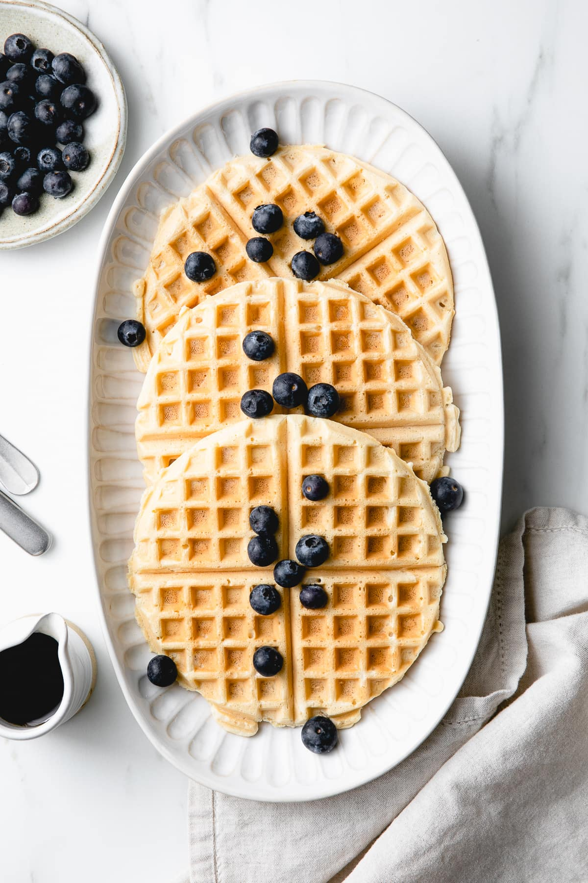 top down view of best vegan waffles on a serving platter with items surrounding.