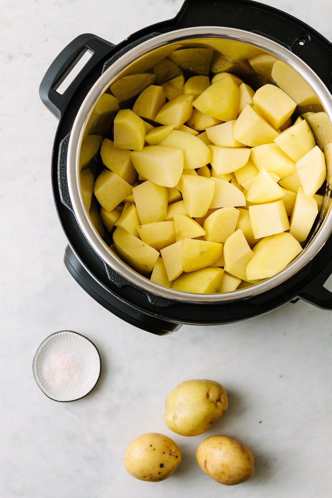 top down view of instant pot with potatoes getting ready to make vegan mashed potatoes.