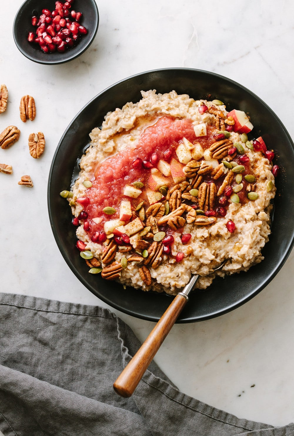 cinnamon oatmeal with applesauce, pecans, apples, pomegranetes in a black bowl