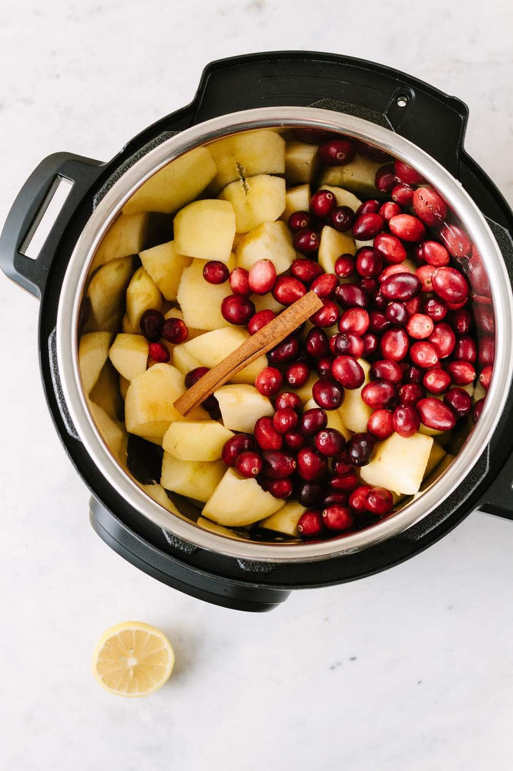 apples and cranberries in and instant pot with a cinnamon stick