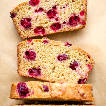 sliced orange cranberry bread on parchment paper