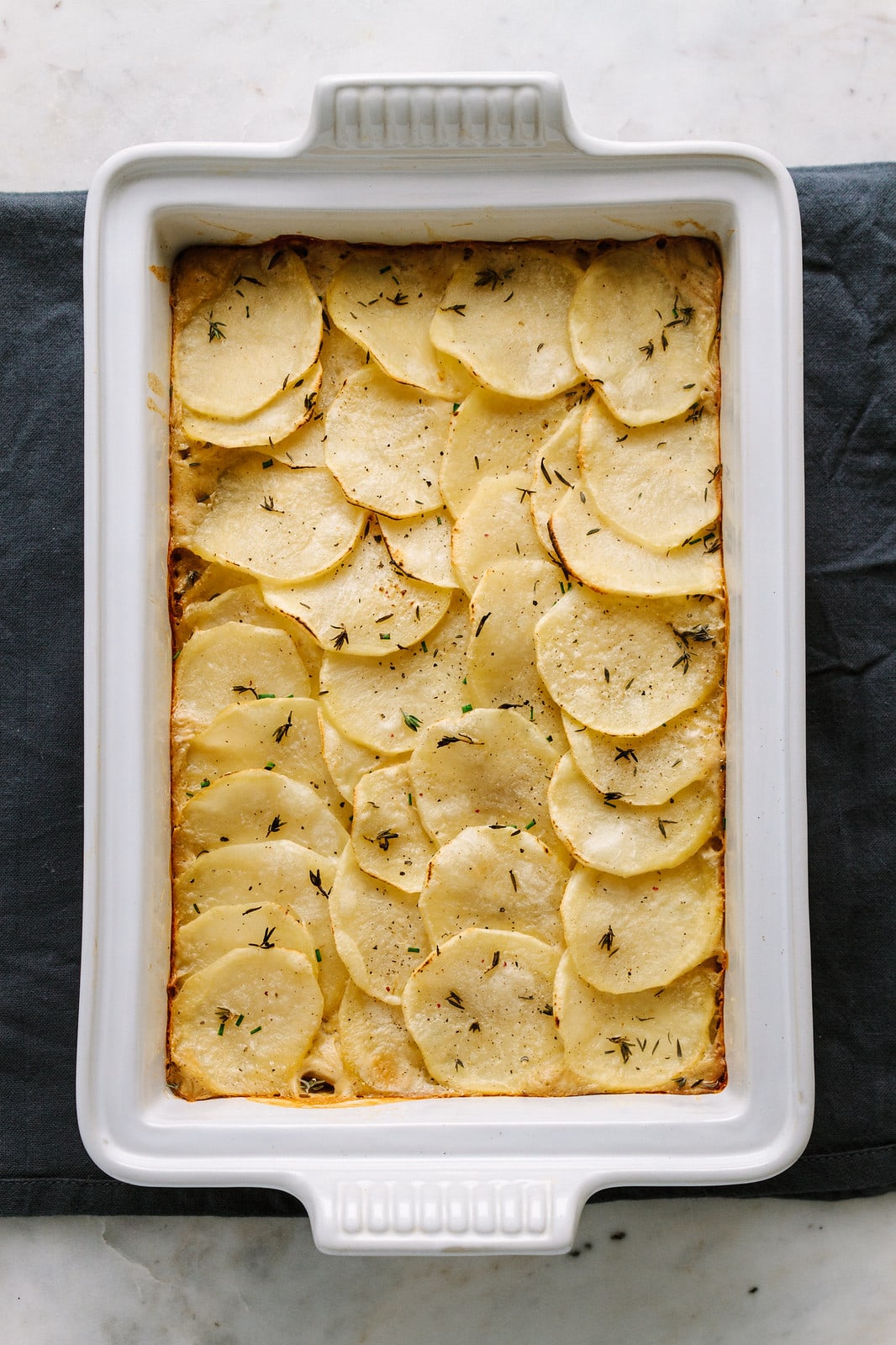 top down view of freshly baked vegan scalloped potatoes in a baking dish.