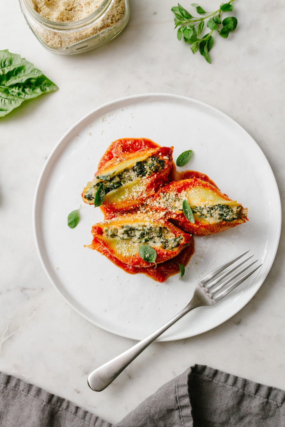 vegan stuffed shells with spinach and ricotta on a white plate with fork