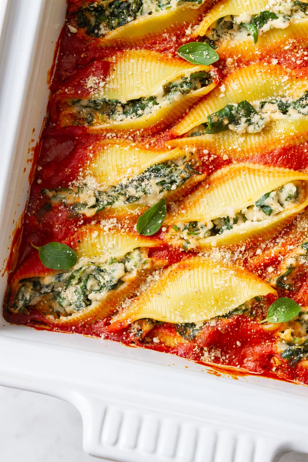 spinach-ricotta stuffed shells in a baking dish just pulled from the oven