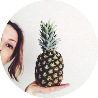 half head shot of julie, the simple veganista, holding a pineapple