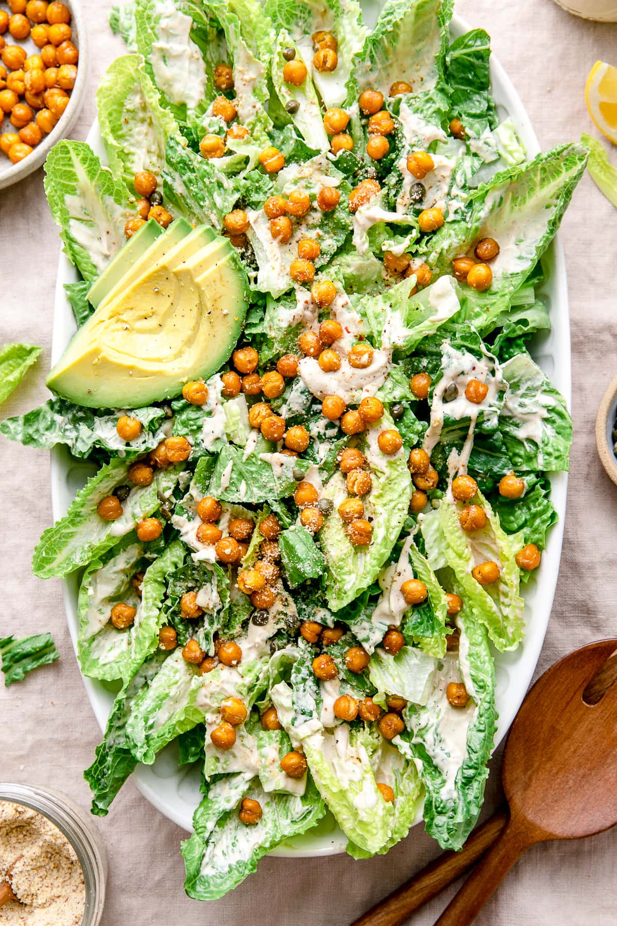 top down view of vegan caesar salad on a platter with items surrounding.