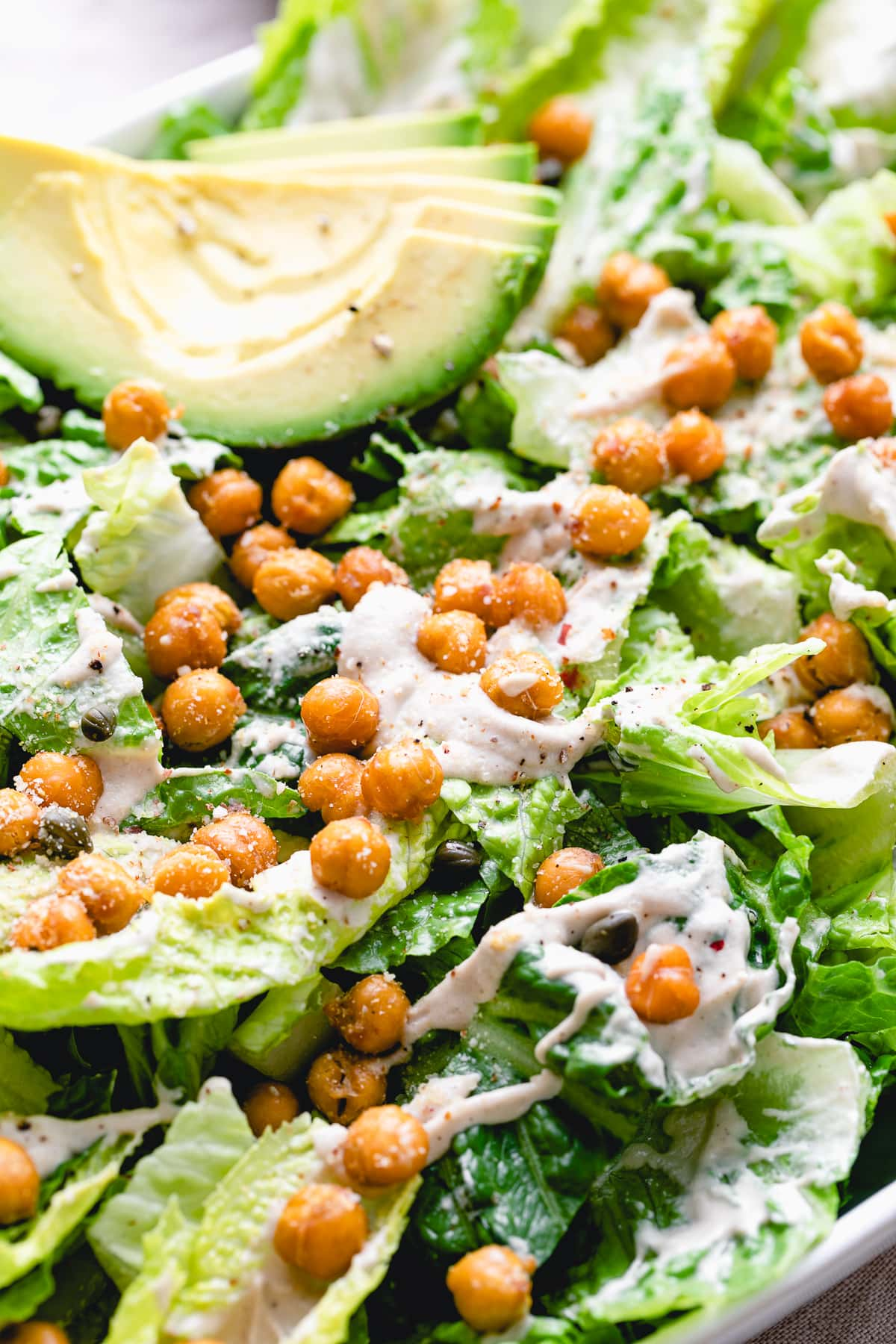 up close side angle view of the best vegan caesar salad with crispy chickpeas and avocado.