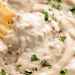 creamy caramelized vegan french onion dip in a bowl with chip