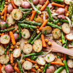 freshly roasted asparagus, potato and chickpea sheet pan dinner with a wooden spatula