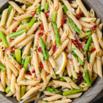 top down view of wooden bowl with garlic lemon asparagus pasta salad.