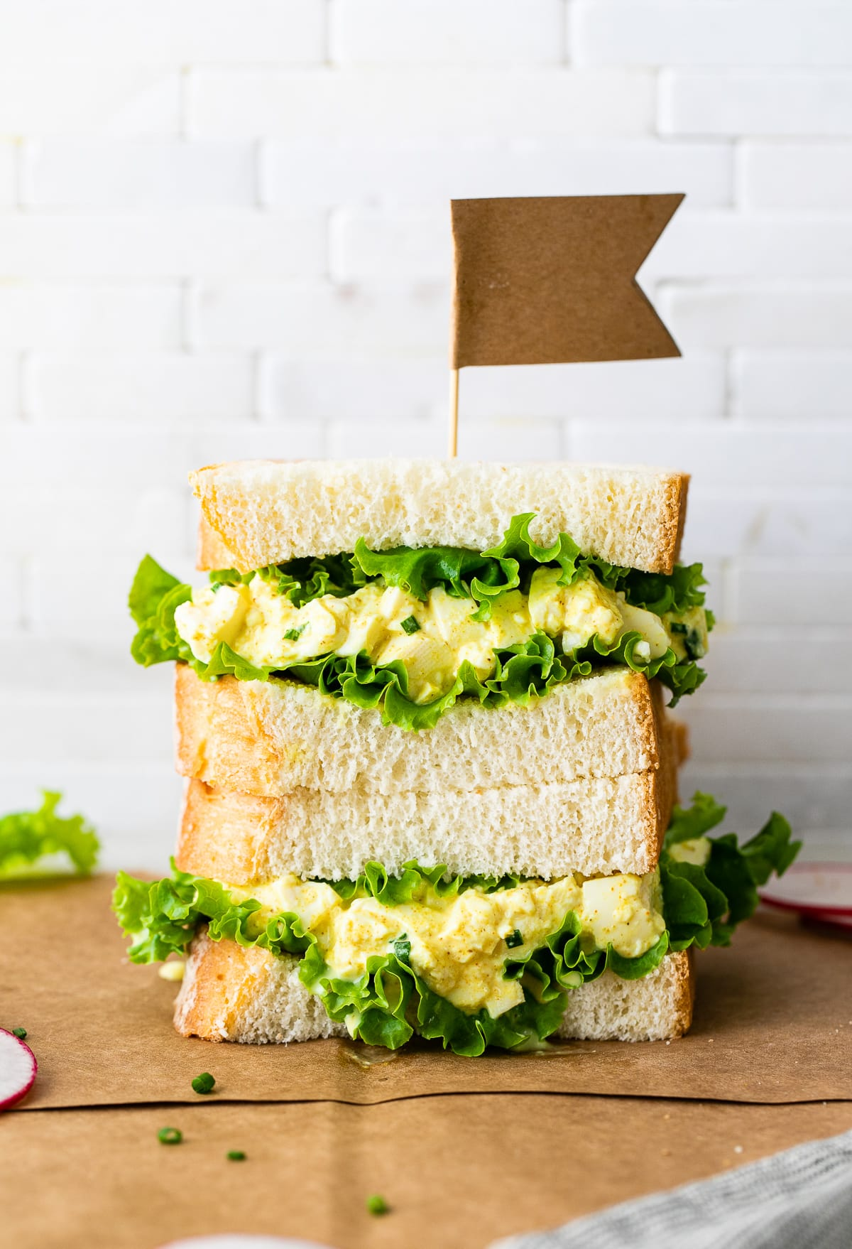 head on view of two halves of vegan egg salad sandwich stacked.