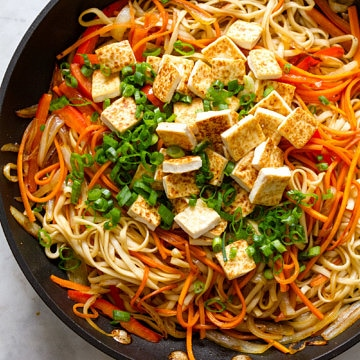 top down view showing the process of making easy vegetable lo mein in a skillet.