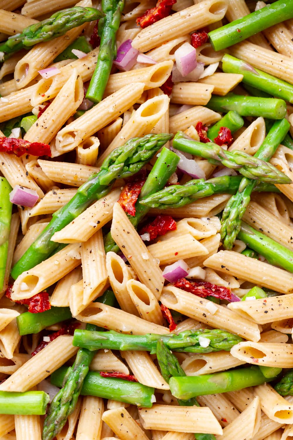 top down close up view of pasta with asparagus, sun dried tomatoes, red onion and zesty garlic lemon dressing freshly tossed together in a white pot