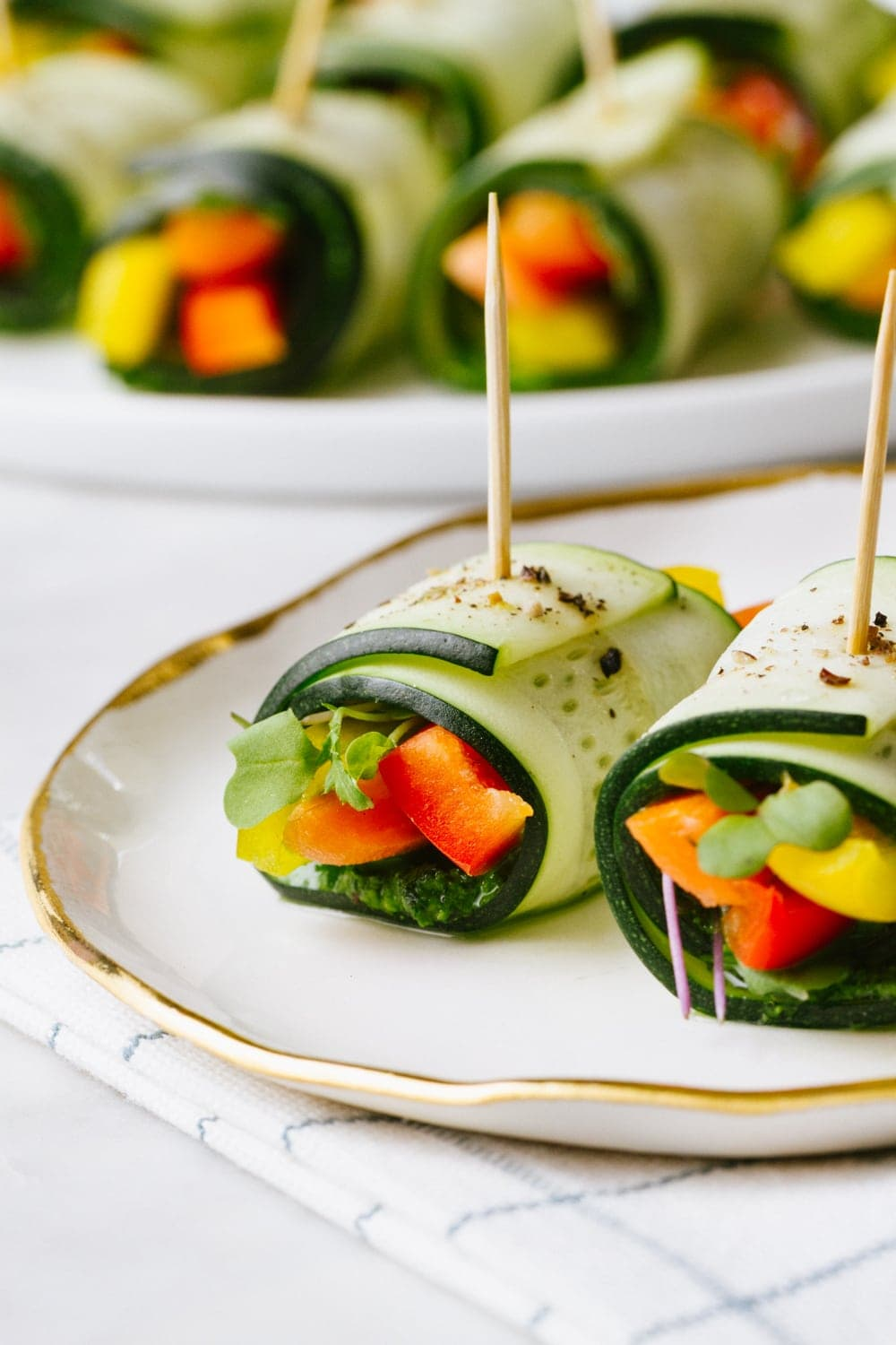 raw zucchini wraps on a white plate