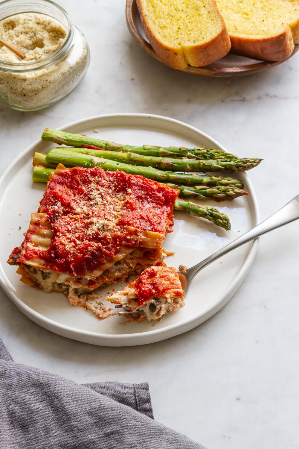 side view of a plate with a slice of simple vegan lasagna and asparagus, with almond parmesan and bread on the side