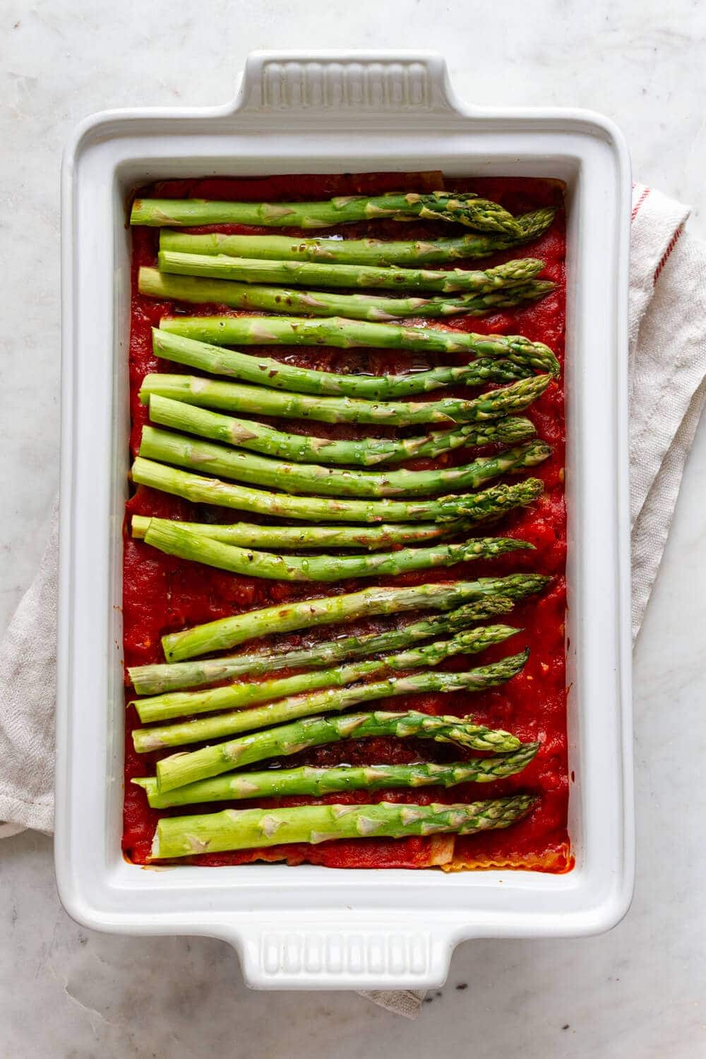 top down view of a white baking dish with assemble and cooked vegan lasagna baked with fresh asparagus on top