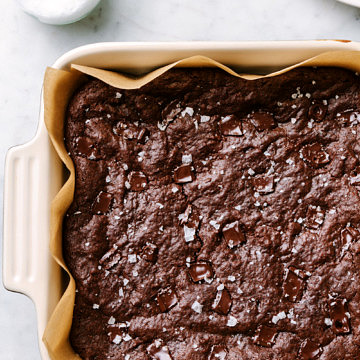 fudgy vegan brownies in a baking dish, fresh from the oven sprinkled with course salt