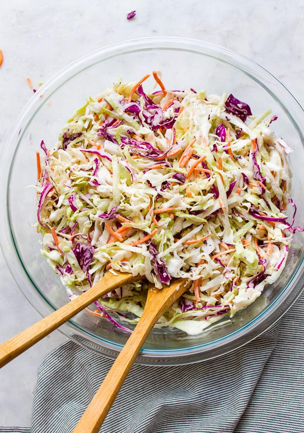 top down view of a glass mixing bowl with freshly made creamy vegan coleslaw.