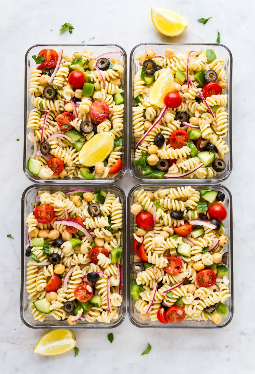 easy vegan pasta salad with lemon slice in individual storage containers for meal prep.
