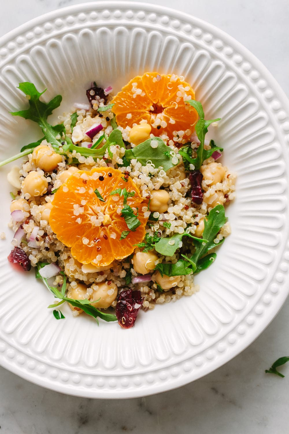 top down view of a serving of quinoa salad in a white bowl.