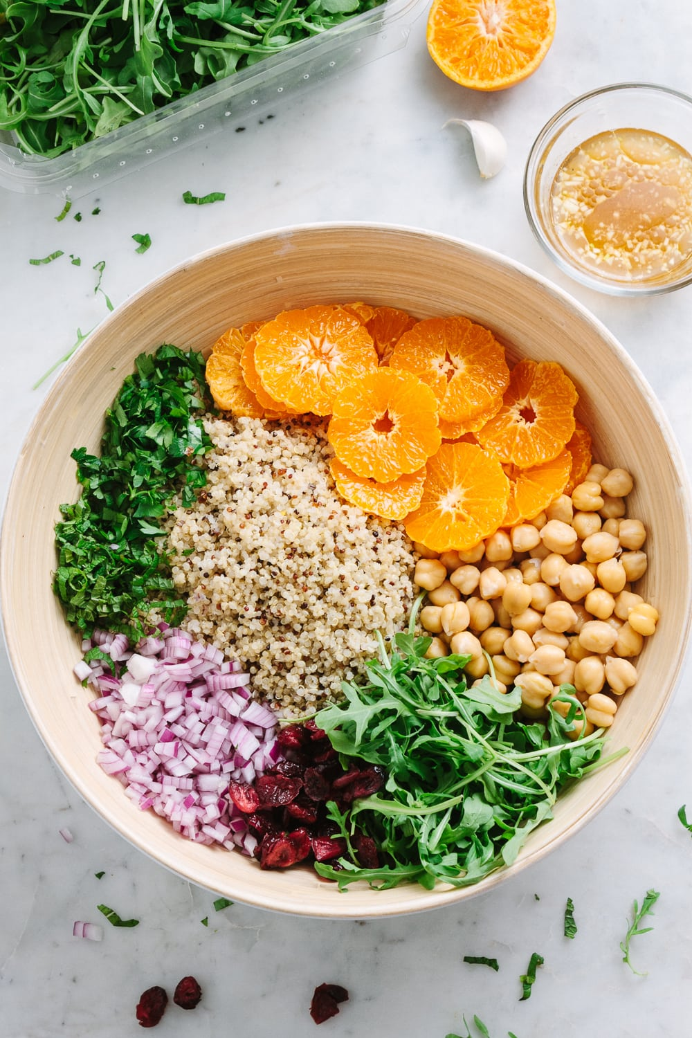 top down view of large bamboo mixing bowl filled with salad ingredients and ready to have dressing poured overtop and tossed.