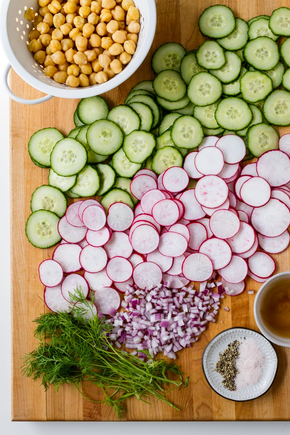 top down view of a wooden cutting board with sliced radishes, cucumbers, diced red onion, whole chickpeas in a small white colander, dill, apple cider vinegar and small dish with salt and pepper