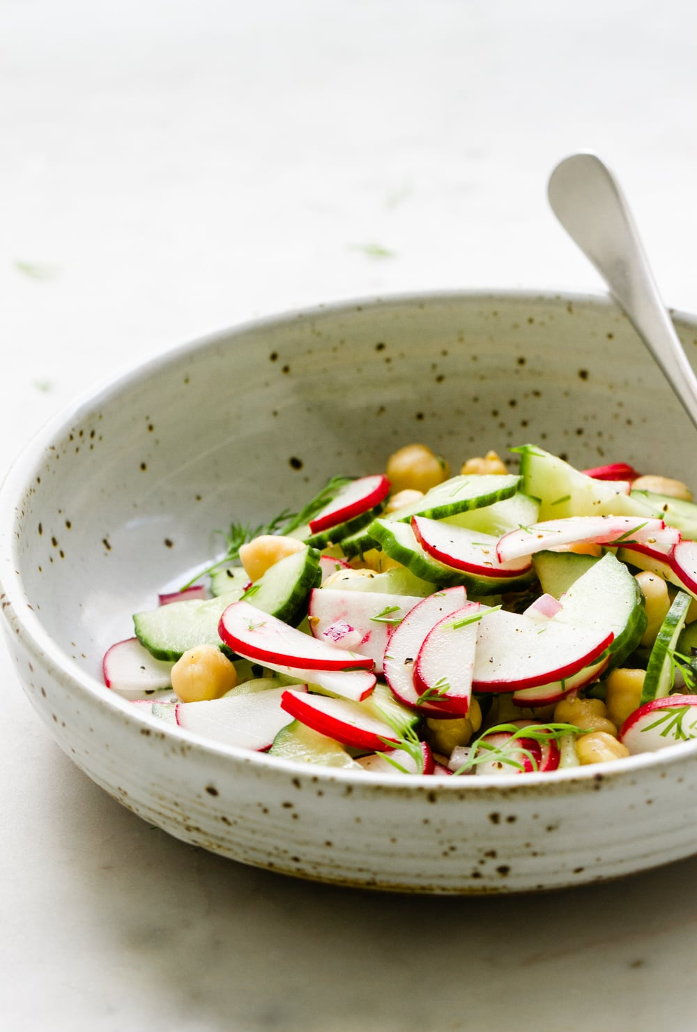 side angel view of a rustic bowl with a serving of radish cucumber salad and spoon on a marble slab