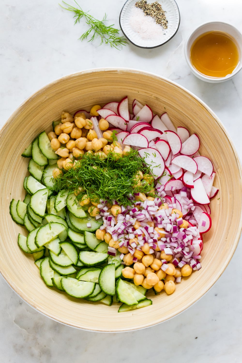 top down view of the ingredients for radish cucumber salad in a mixing bowl with the dressing in a small bowl to the upper ride side