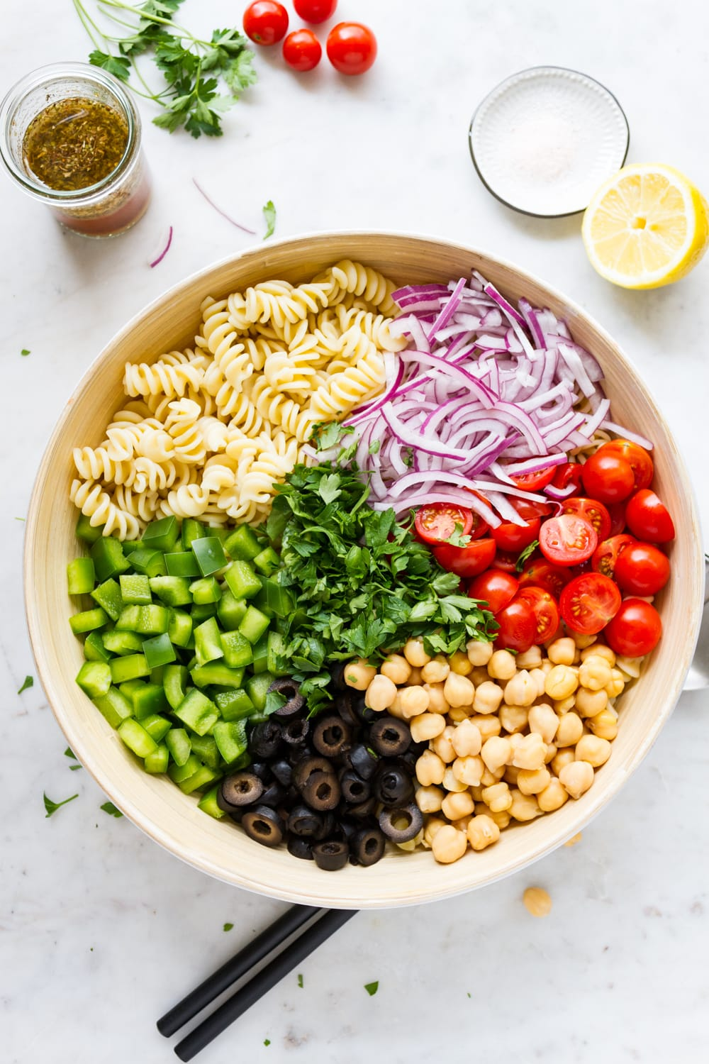 top down view of large mixing bowl with individual ingredients for vegan pasta salad added.