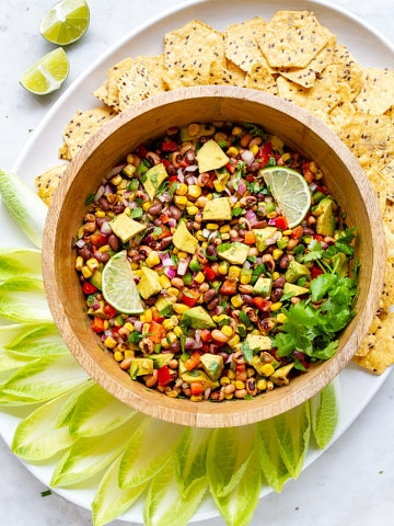 top down view of a platter with bowl full of cowboy caviar surrounded by endive and tortilla chips for scooping.