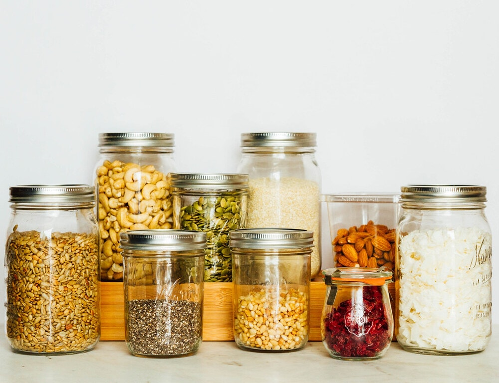 mason jars filled with an assortment of dried nuts, seeds, and dried fruits.
