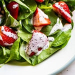small plate with a spinach-strawberry salad topped with creamy vegan poppy seed dressing.