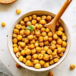 top down view of bowl full of crispy roasted chickpeas with wooden spoon for scooping.