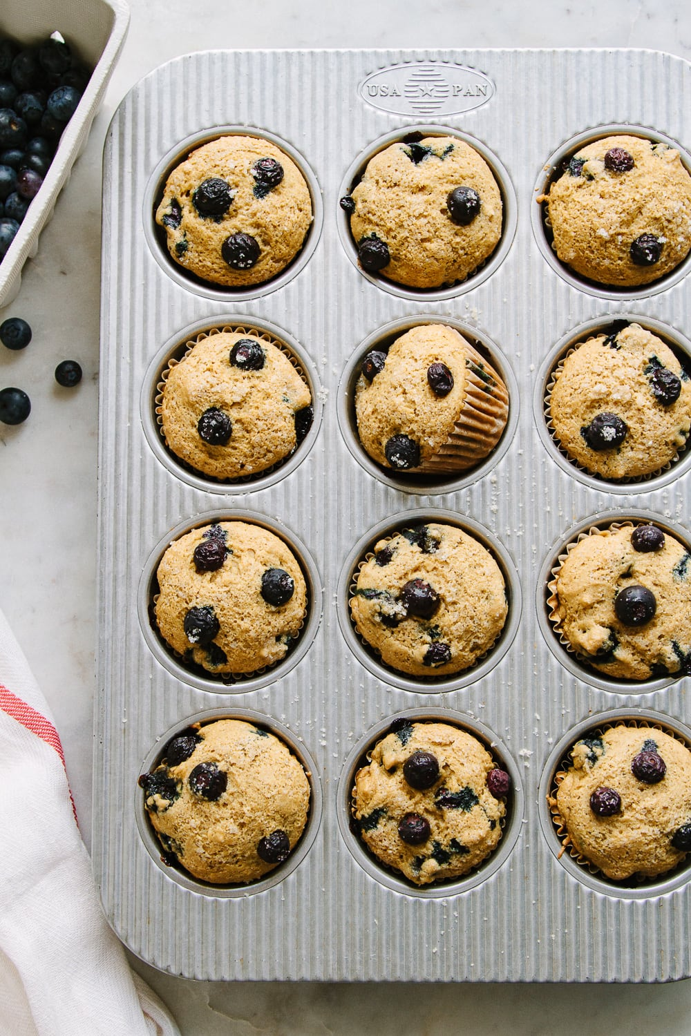 top down view of vegan blueberry muffins in a muffin tin just pulled from the oven.