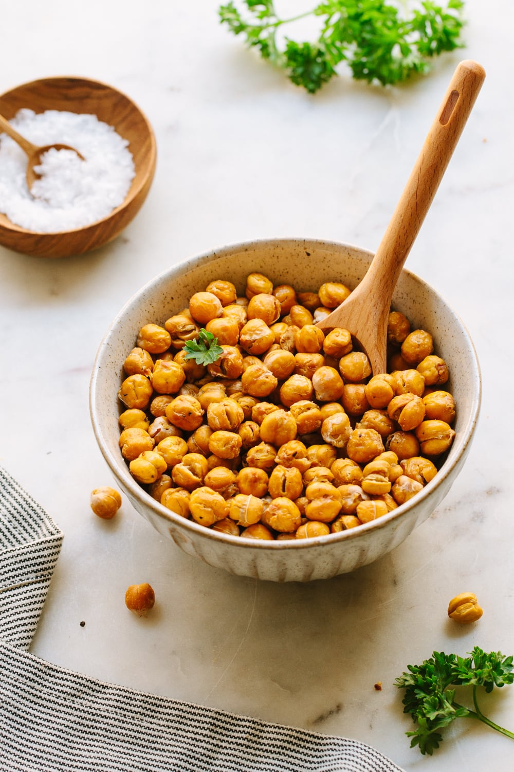 side angle view of bowl full of crispy roasted chickpeas with wooden spoon for scooping.