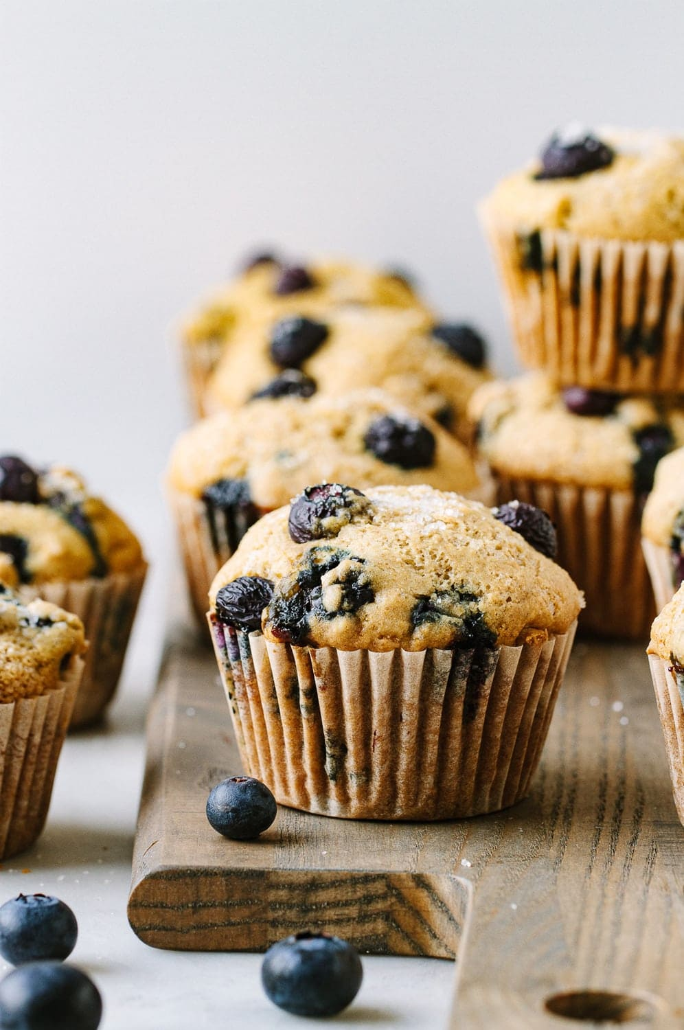 head on shot of vegan blueberry muffins on a wooden serving board.