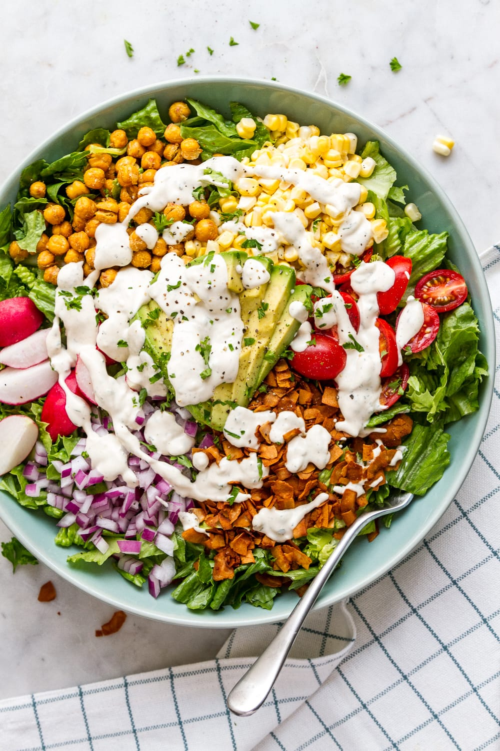 top down view of bowl filled with vegan cobb salad drizzled with vegan ranch dressing.