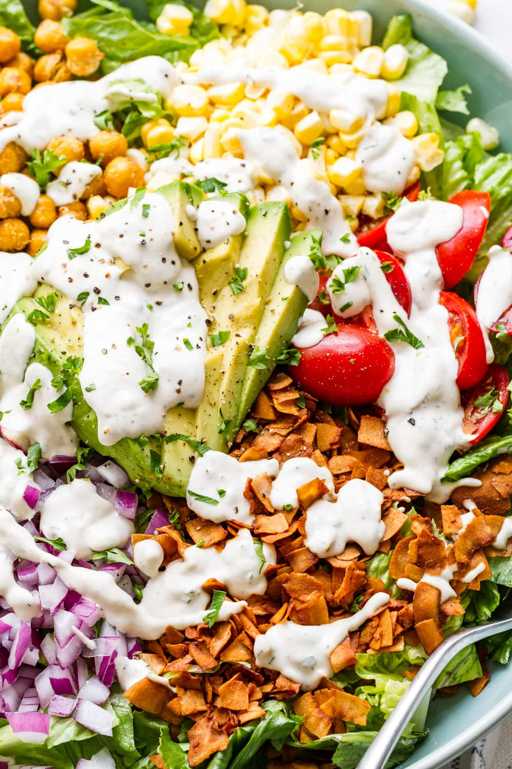 up close side angle view of vegan cobb salad with vegan ranch dressing.