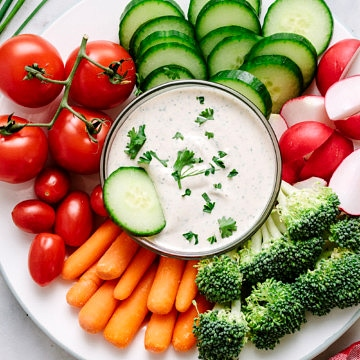 top down view of a platter plate with fresh veggies and small bowl of easy vegan ranch dressing-dip in the center with dipped cucumber.