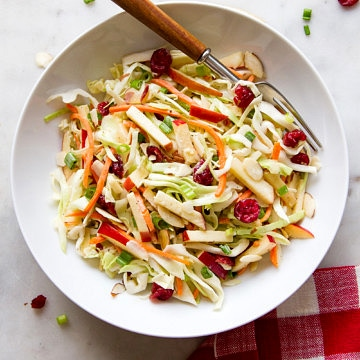 top down view of best apple coleslaw in a white serving bowl with wooden fork.