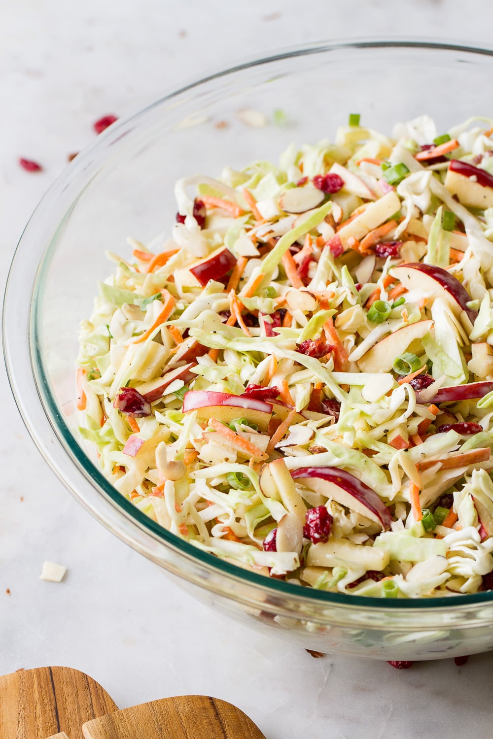side angle view of freshly mixed easy apple coleslaw in a glass bowl.