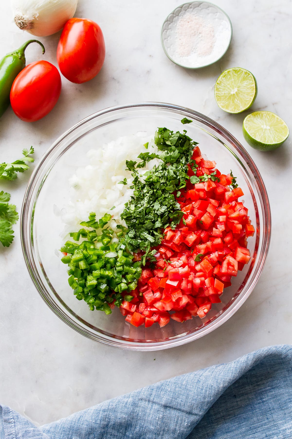 top down view of pico de gallo ingredients added to a glass mixing bowl before mixing to combine.