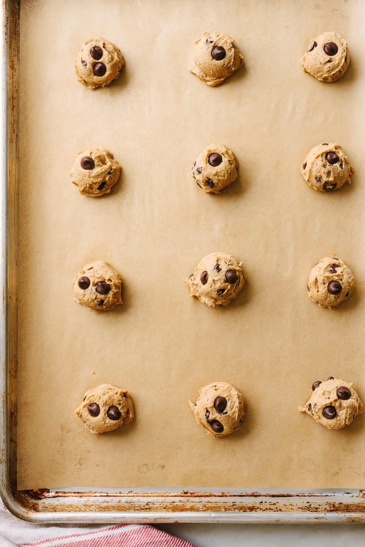 top down view of raw vegan cookie dough mounds on baking sheet.
