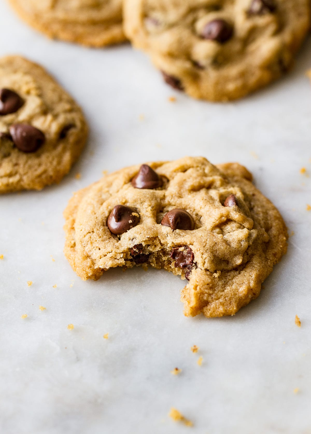 side angle view of chocolate chip cookie with bite taken.