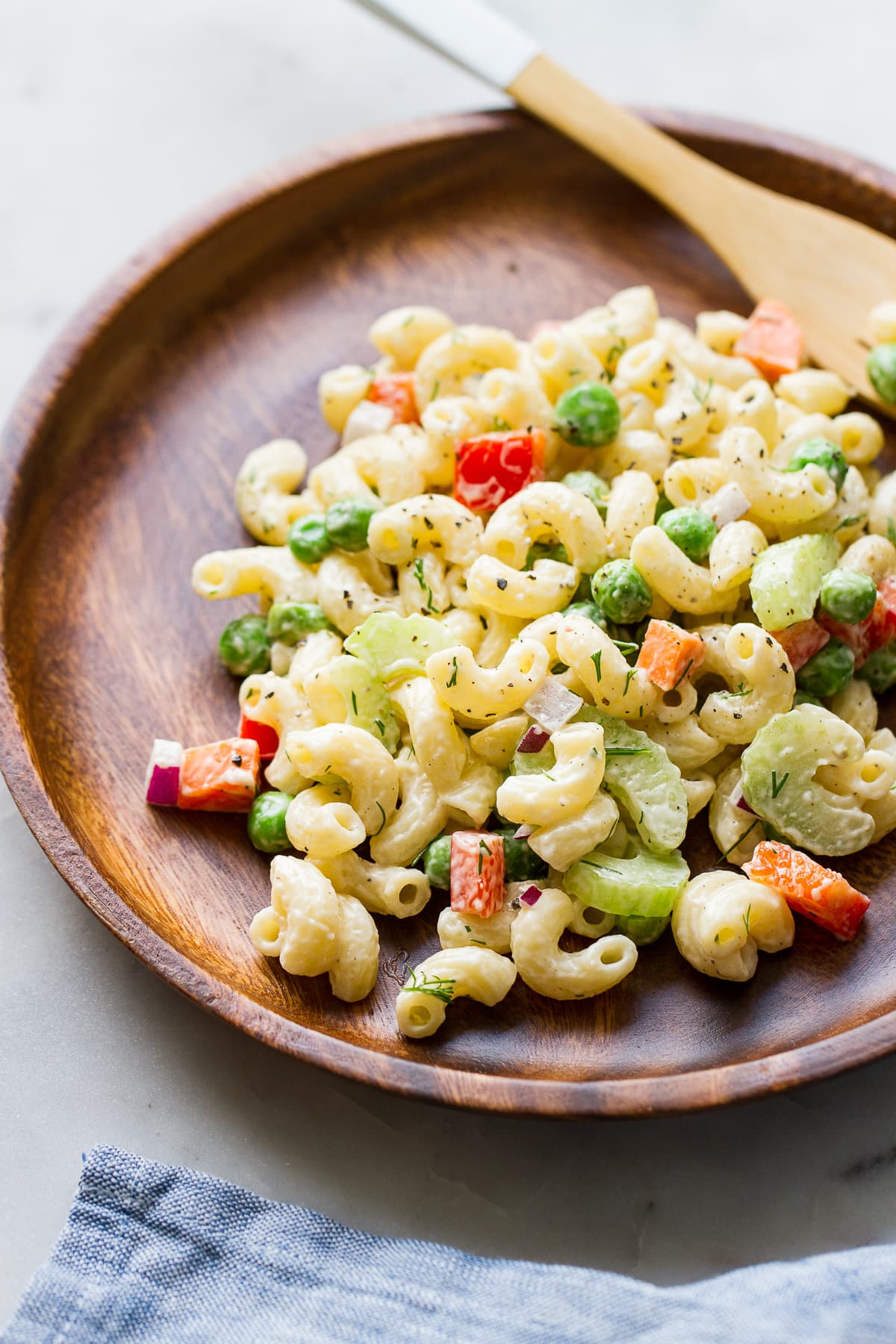 top down view of a serving of creamy vegan macaroni salad in a wooden plate.
