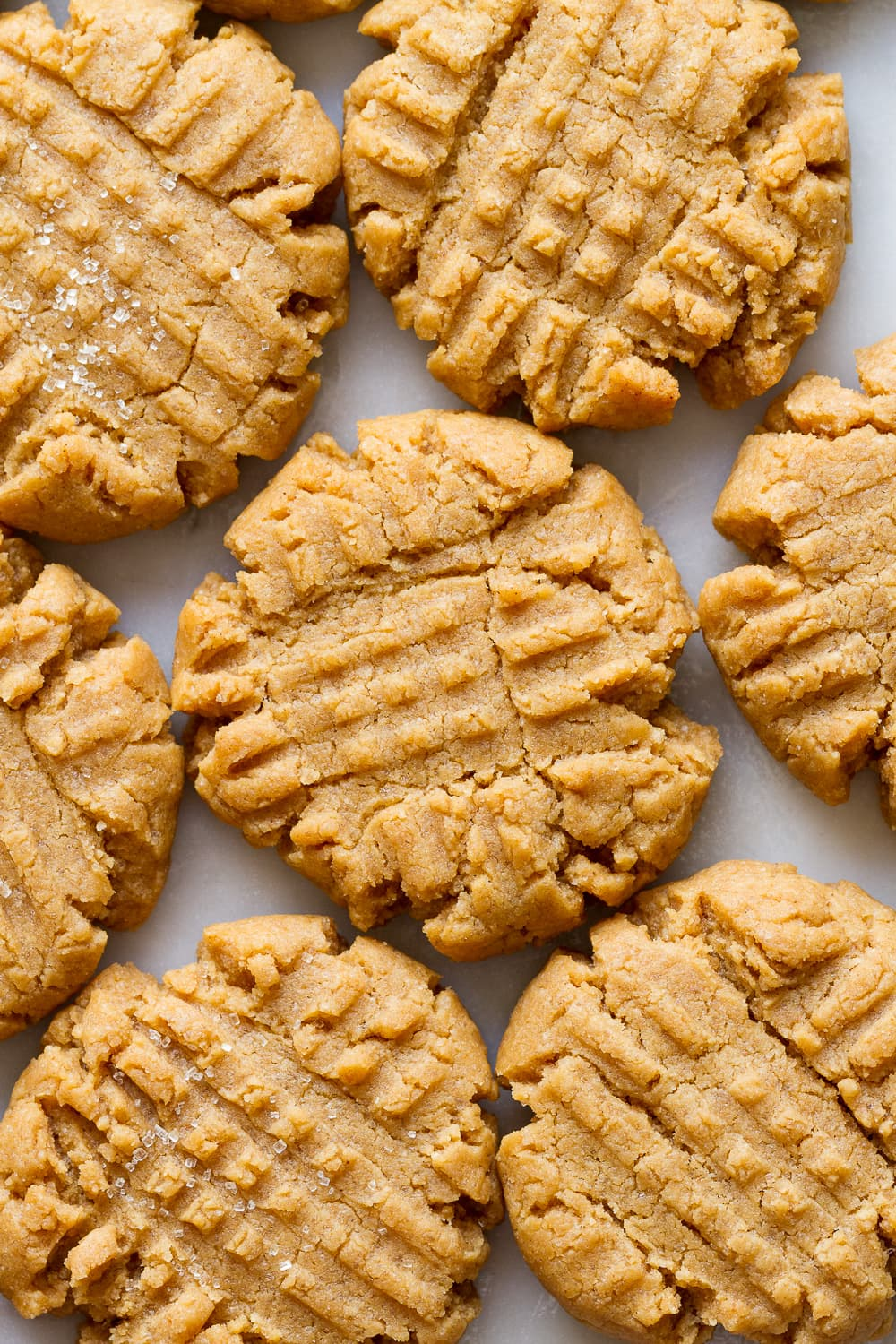 up close view of a cluster of vegan peanut butter cookies on a marble slab.