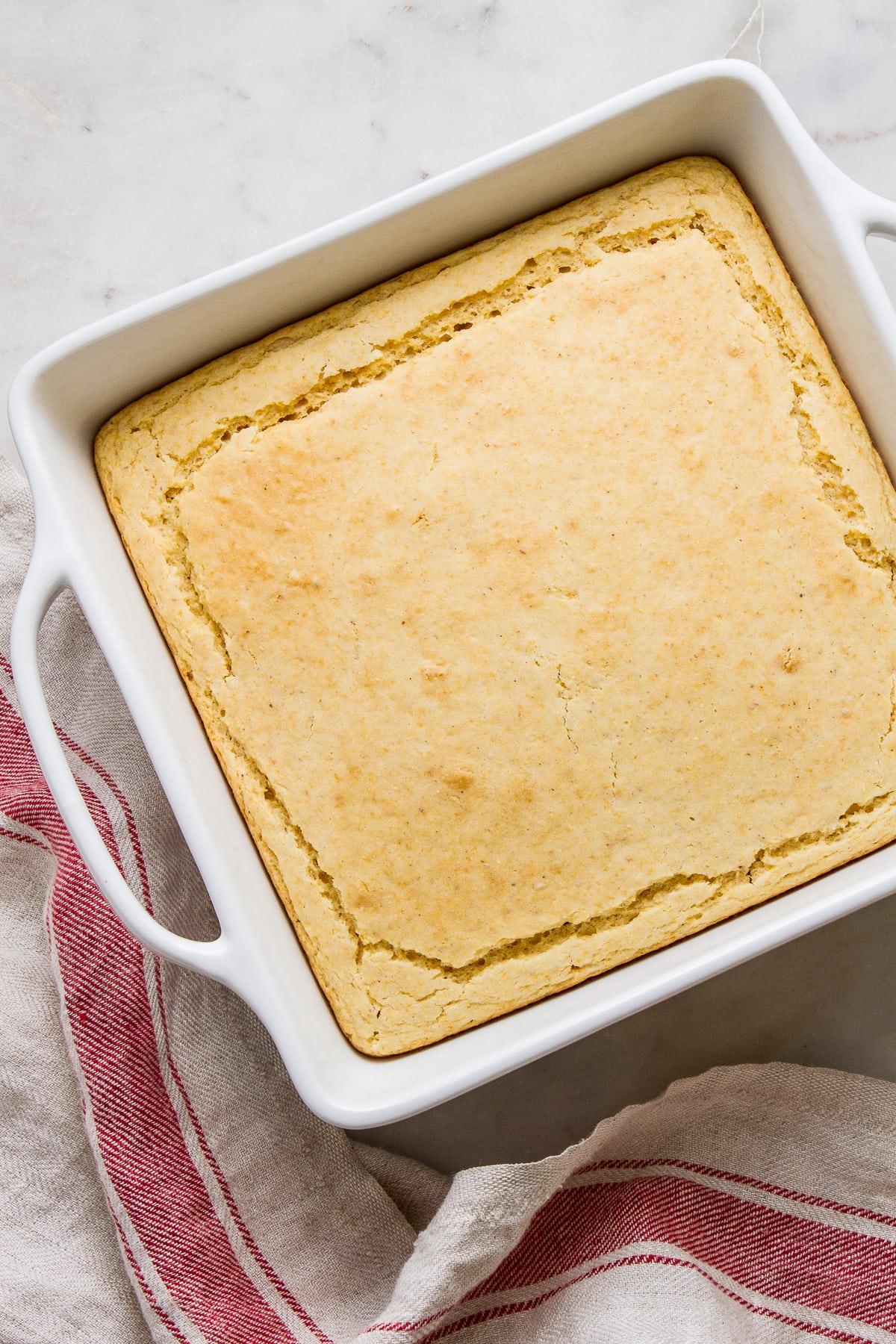 top down view of freshly baked vegan cornbread in a white baking dish.