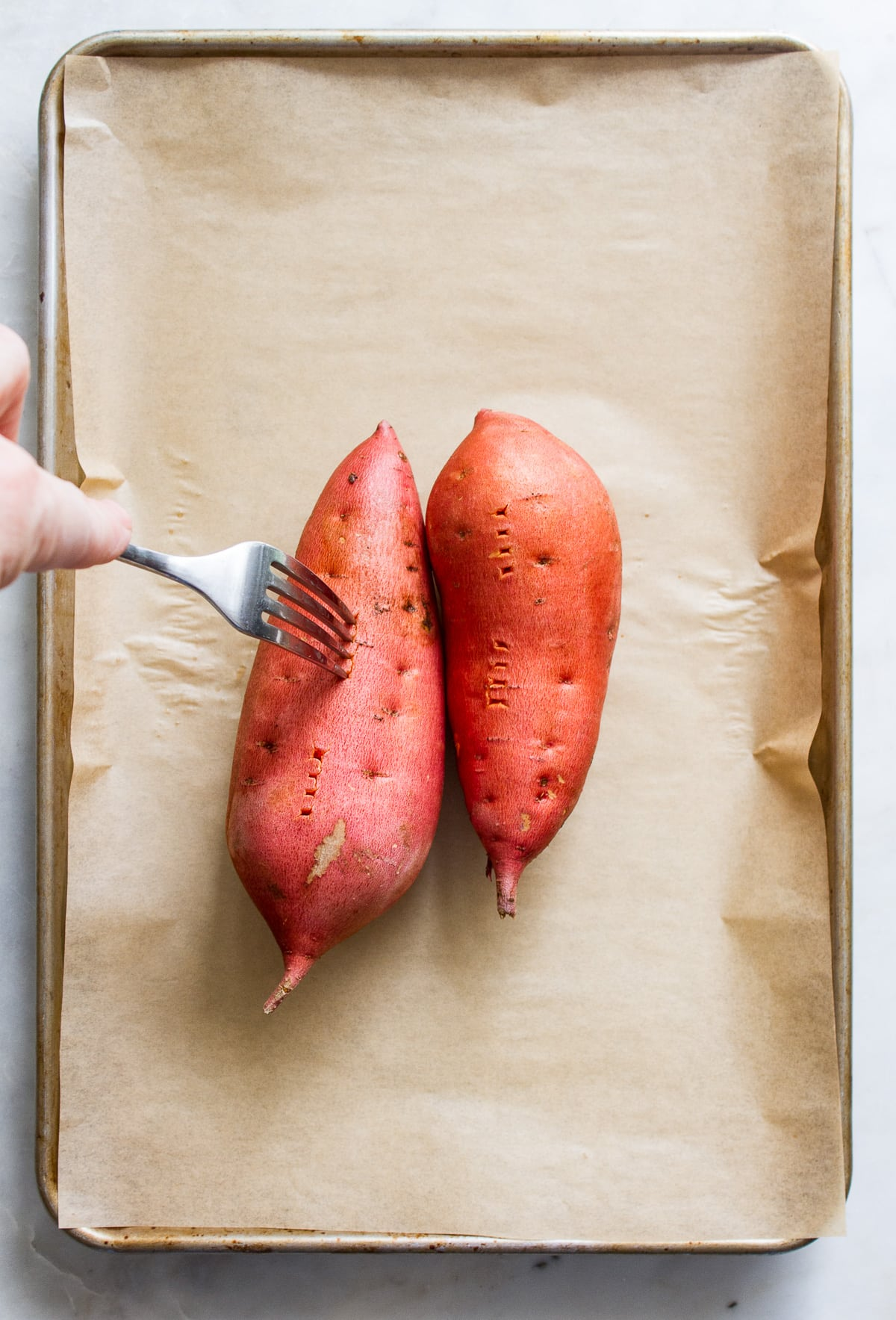 top down view of 2 sweet potatoes on a rimmed baking sheet with holes poked using a fork.