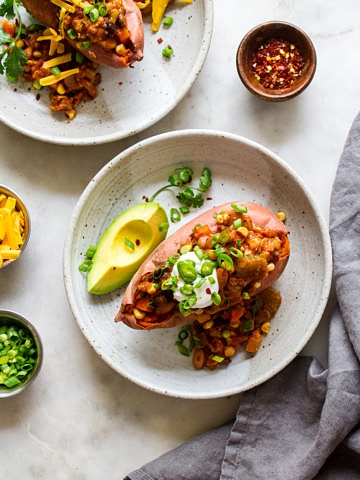 top down view of chili stuffed sweet potato in a shallow serving bowl.